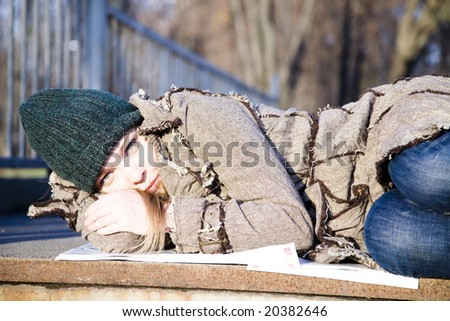 The Woman Lying On The Newspaper. Economic Crisis Series - stock photo