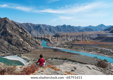 The woman meditates on a grief over the mountain river