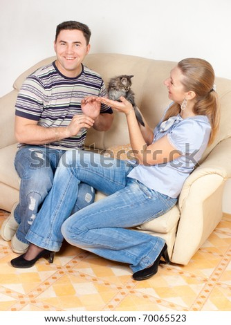 The woman offers a kitten to the man, an interior