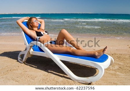 The woman on a plank bed at the sea - stock photo