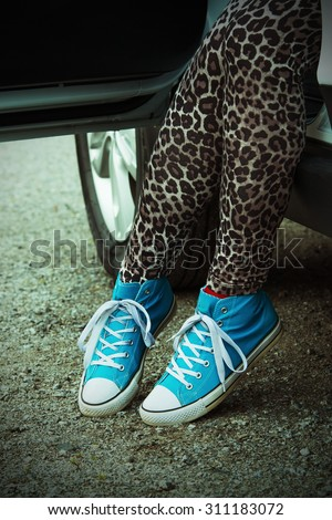 The woman rising out of the car with blue sneakers in Finland. She is wearing a leopard-print pants. Image includes a lomo-blue effect.