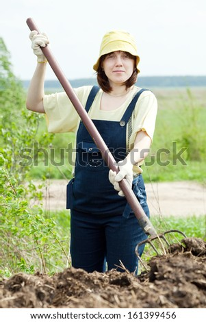 The woman scatters the manure pitchfork in the field - stock photo