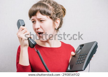 The woman shouts into the phone wired telephone. On a gray background. - stock photo