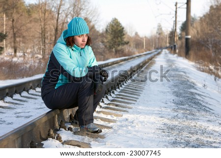 The woman sitting on rails of the railway in the winter - stock photo