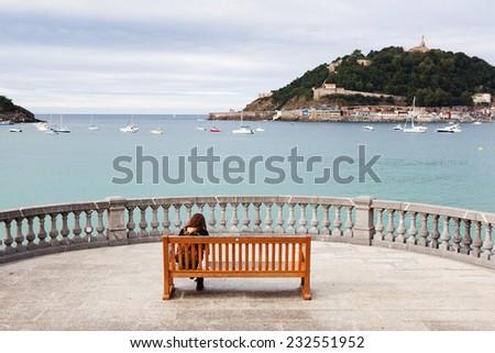 The woman sitting on the bench in San Sebastian. - stock photo