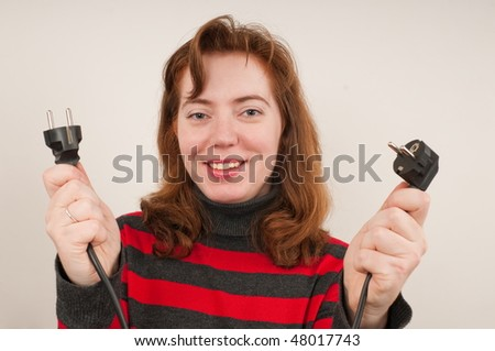 The woman smiles and has control over two plugs. - stock photo