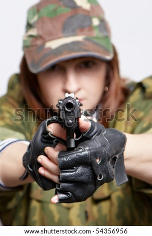 The woman soldier with a pistol in hands on a light background