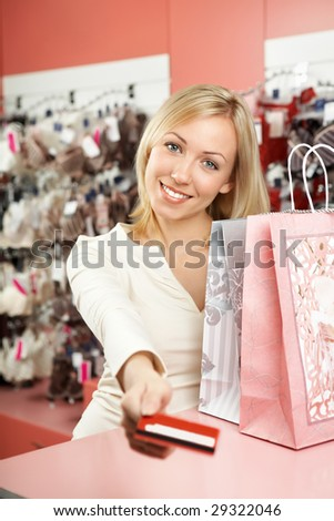 The woman stretches forward a card for payment of purchases at a counter - stock photo