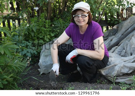 The woman the gardener in a garden weeding vegetables