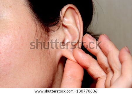 the woman touches by fingers of a hand of a lobe of an ear - stock photo