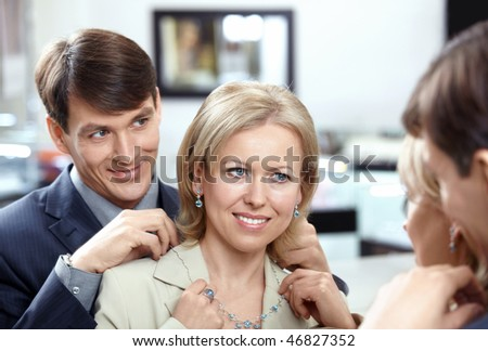 The woman tries on a necklace at a mirror in shop - stock photo
