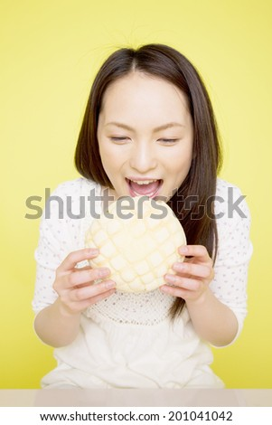 The woman trying to eat a melon bread