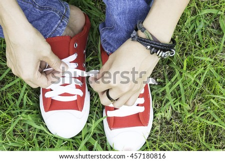 The woman wear blue jeans are the red sneakers lace up the lawn. - stock photo