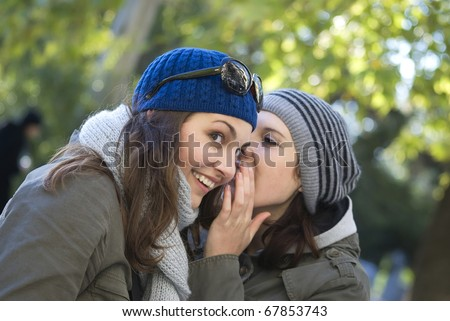 The woman whispers in ear to other woman - stock photo