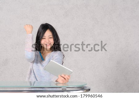 The woman who is pleased to watch a tablet PC