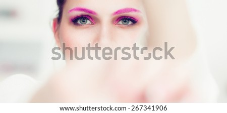 The woman with a bright pink make-up and pink eyebrows hides the face in hands. Studio portrait. - stock photo