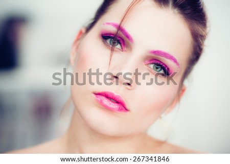 The woman with a bright pink make-up. Studio portrait. - stock photo