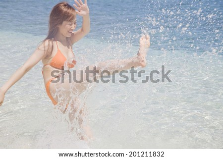 The woman with a swimming suit smiles while playing in the sea