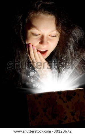The woman with abstract light from a gift box. Emotion a surprise. A dark background - stock photo