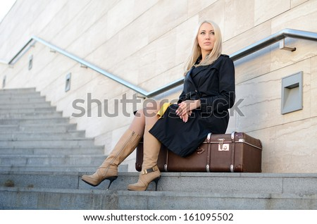 The woman with suitcase a brick wall
