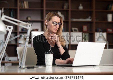 The woman working at the table. Talking on the phone - stock photo