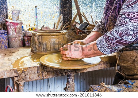 The women is producing the pottery with soft clay