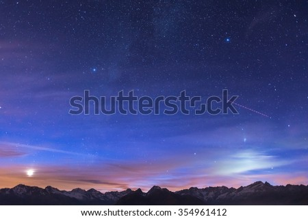 The wonderful starry sky on Christmas time and the majestic mountain range of the Italian French Alps, with glowing villages below and moonlight behind the clouds. Some digital noise due to high iso. - stock photo