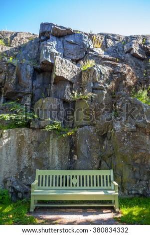 The wooden bench in Helsinki park against granite rock - stock photo