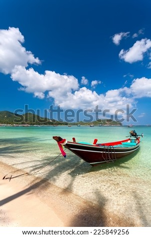 the wooden boat under a palm tree shadow on the sandy coast. - stock photo