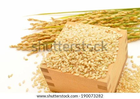 The wooden box is overflowing with beige seeds. - stock photo