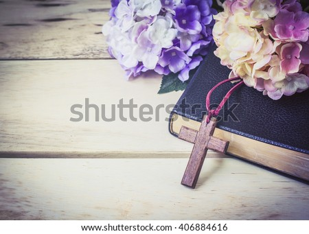 The wooden cross and black bible with flowers on wooden background - stock photo