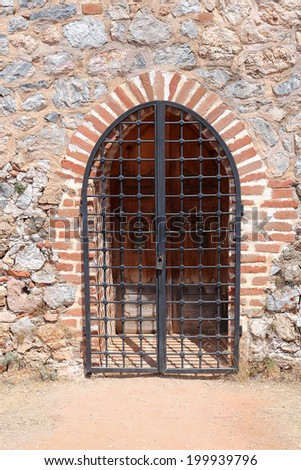 The wooden gate locked with steel grating front view - stock photo