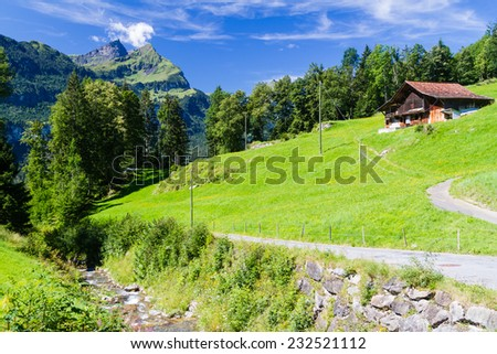 The wooden house amongst the Swiss Alps. - stock photo