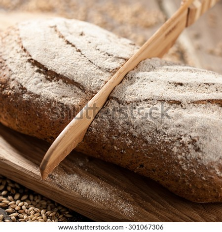The wooden knife cuts the loaf of bread on cutting board, close up - stock photo