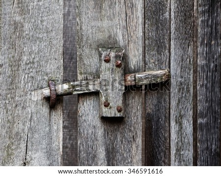 The wooden latch on an old wooden door - stock photo