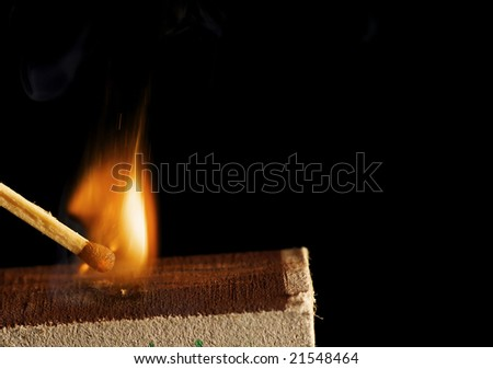 The wooden match is lighted from a box - stock photo