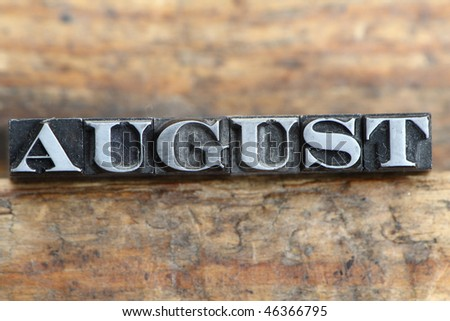 the word august in letterpress type on a wooden background. - stock photo