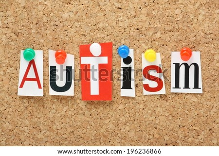 The word Autism in cut out magazine letters pinned to a cork notice board - stock photo