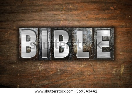 """The word """"Bible"""" written in vintage metal letterpress type on an aged wooden background. - stock photo"""