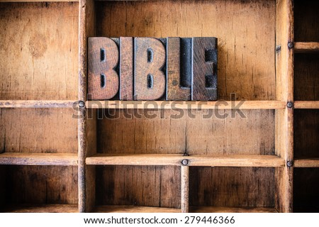 The word BIBLE written in vintage wooden letterpress type in a wooden type drawer. - stock photo