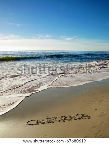 "the word ""California"" written in the wet sand on the world famous Laguna Beach in southern california beach with a blue sky and nice tide and waves from the pacific ocean - stock photo"