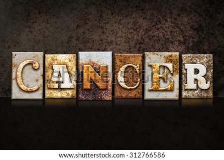 """The word """"CANCER"""" written in rusty metal letterpress type on a dark textured grunge background. - stock photo"""