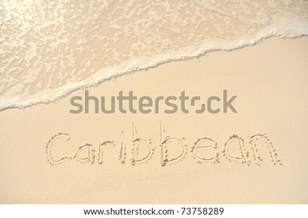 The Word Caribbean Written in the Sand on a Beach - stock photo