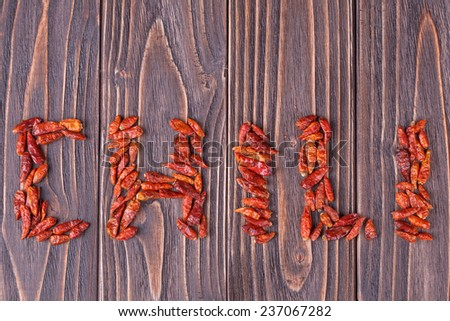 """the word """"chili"""" written with red chili pepper  on a wooden background - stock photo"""