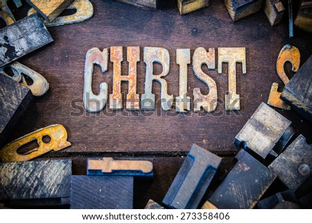 The word CHRIST written in rusted metal letters surrounded by vintage wooden and metal letterpress type. - stock photo