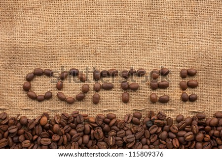 The word coffee made from coffee beans on sackcloth next to coffee beans - stock photo