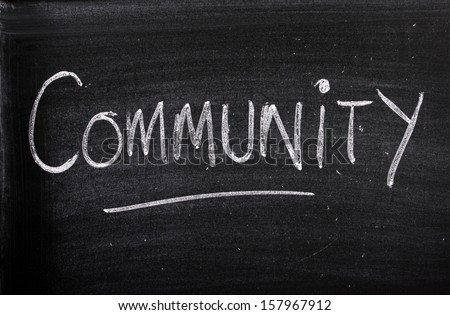 The word Community written on a well used blackboard in white chalk.