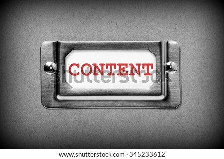 The word Content in red text on a drawer label in a metal holder as part of a filing system. Processed in black and white for effect