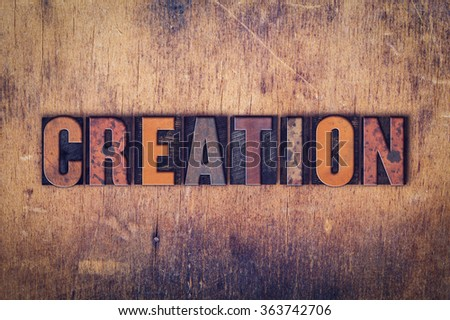 """The word """"Creation"""" written in dirty vintage letterpress type on a aged wooden background. - stock photo"""