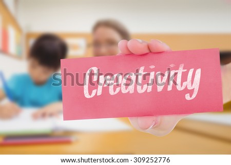 The word creativity and hand showing card against pretty teacher helping pupil in classroom - stock photo